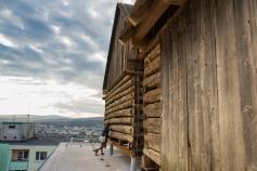 Stodoly reprezentujú vidiecku architektúru, ktorú autor umiestnil na strechu typického 13 poschodového paneláku.
